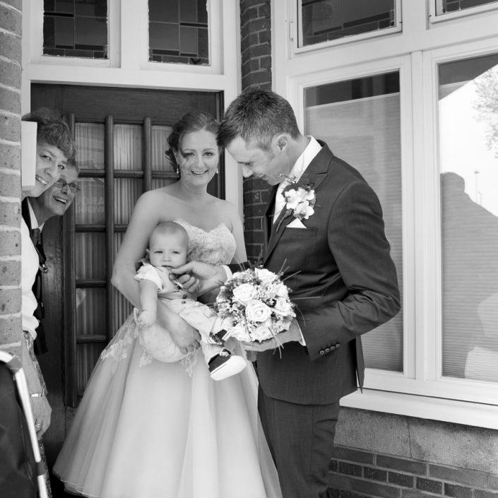 Een spontane trouwfoto van de bruidegom die zijn bruid thuis ophaald.