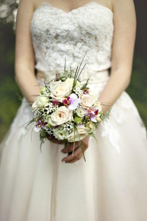 Een klassieke foto van de bruid die haar bruidsboeket vasthoudt.