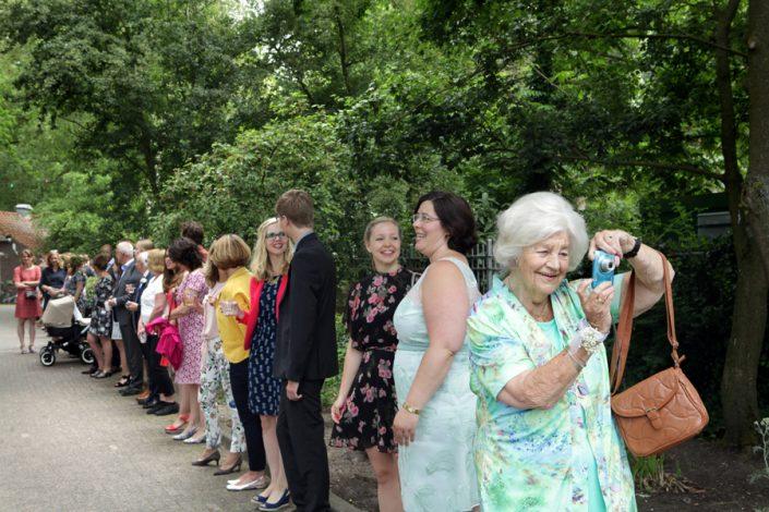 De gasten van de bruiloft wachten in een rij op het bruidspaar. Een grappige foto vanwege de oma met haar camera.