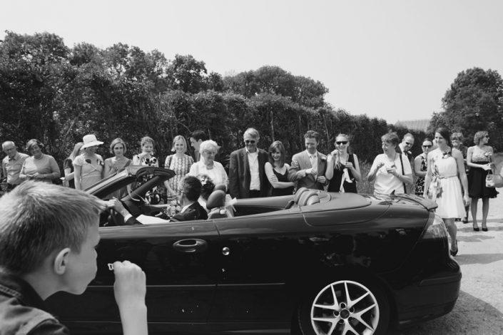 De bruid en bruidegom komen in een sportauto aangereden.