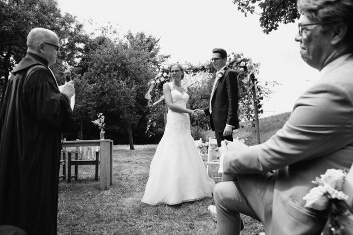 Een spontane trouwfoto van het bruidspaar dat elkaar het ja-woord geeft op een landelijke trouwlocatie.