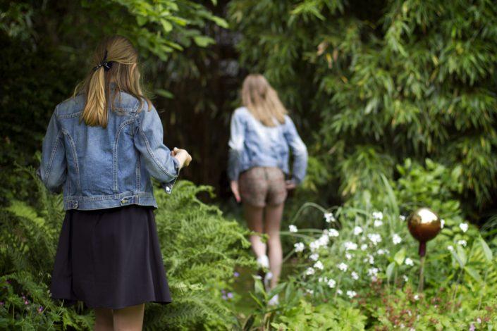 Trouwfotograaf Amsterdam. Een eigenzinnige foto van twee meisjes die door de bosjes lopen.