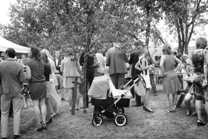 Een grappige bruidsfoto van een kinderwagen op het gras tussen de gasten.