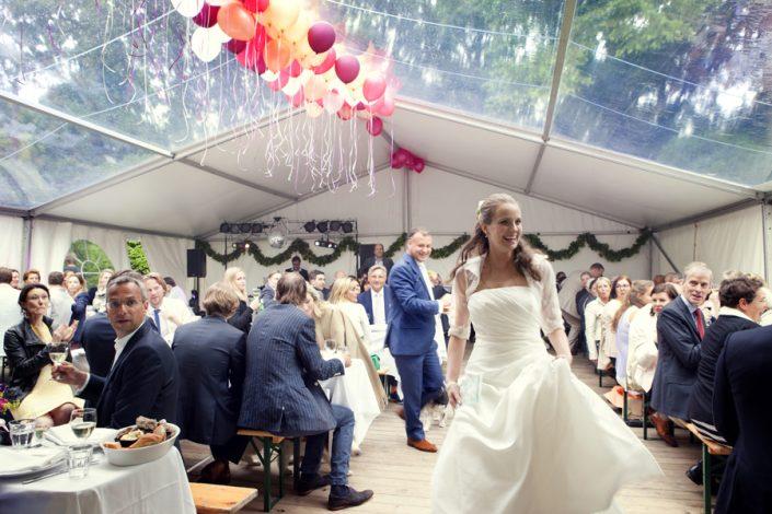 Een prachtige trouwfoto van de bruid die door de witte trouwtent loopt. Een foto van Sophie de Kort bruidsfotografie.