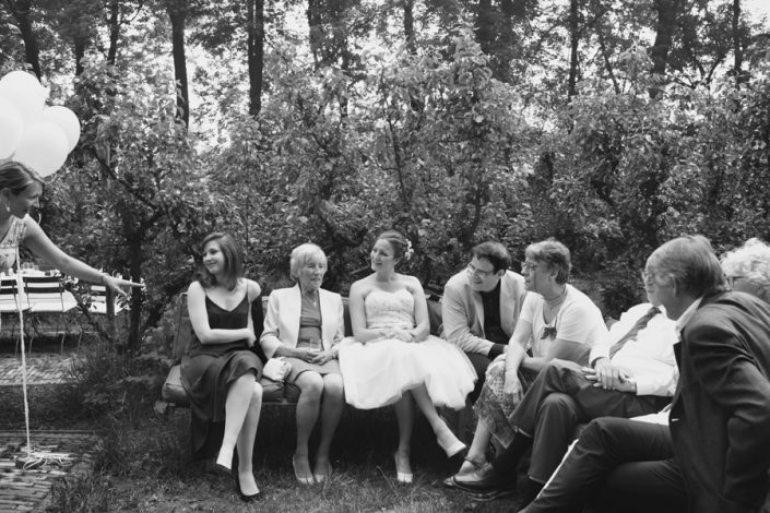 De bruid zit met haar familie op een bankje tussen de bomen op de trouwlocatie.