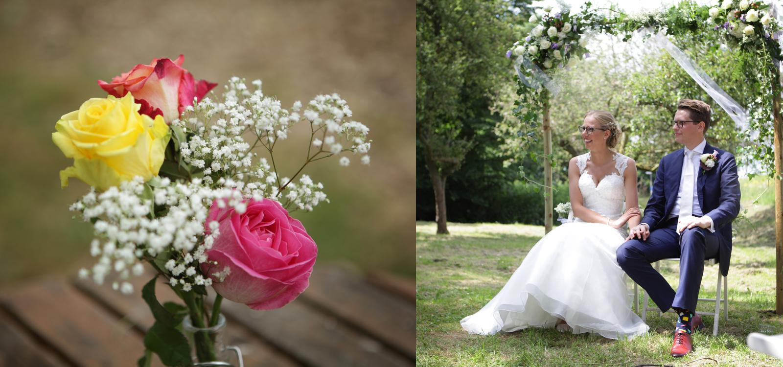 Huwelijksfotografie van een huwelijk tussen de bomen. Het bruidspaar zit onder een bloemenpoort.
